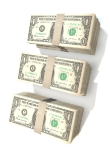 A stack of three bundles of money illustrating how to save time and money with hiring management software.