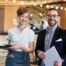 Group portrait of cheerful bearded restaurant manager, and pretty waitress posing for photography while standing against bar counter illustrating the success restaurant operators can have when hiring restaurant employees through WOTC.