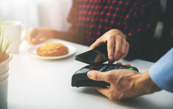 woman using pay-at-the-table EMV reader to process bill with smartphone at cafe